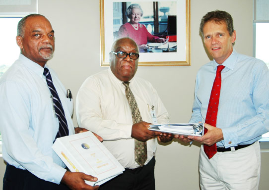 (L-R) Deputy Supervisor of Elections Colford Scott and Training Officer Rupert McCoy present the new manual to His Excellency the Governor.