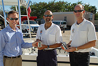 DoE's Research Officer Bradley Johnson (center) and Deputy Director of Research Timothy Austin (right) gladly accept the donation of two Nautilus Lifelines from local distributor Gary Redfern.