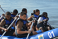 Cadets demonstrate teamwork skills in a water rafting activity.